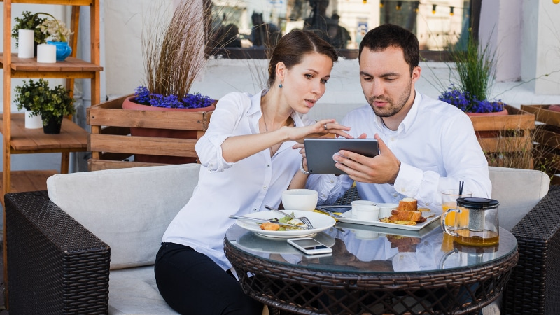 Business people looking at digital tablet in cafe during a meeting.